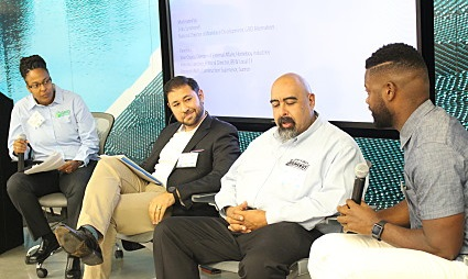 Four people in panel seating discuss a topic