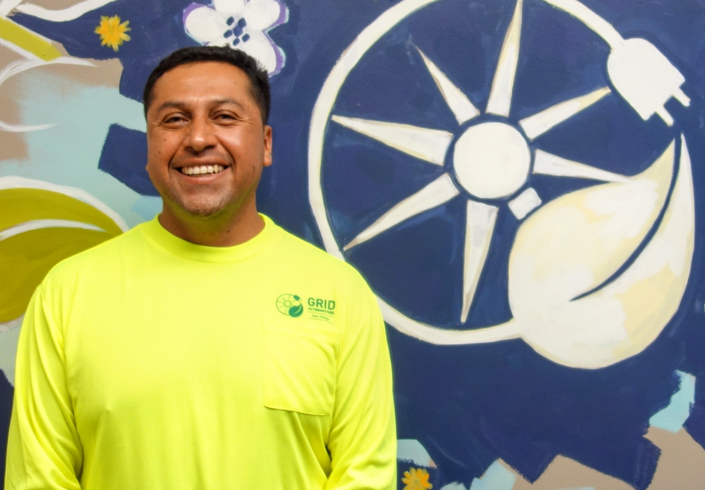 Photo of Luis smiling in front of a GRID mural