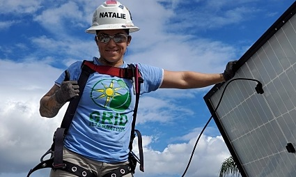 A person in GRID Alternatives clothing and personal protective equipment gives a thumbs-up with a solar panel