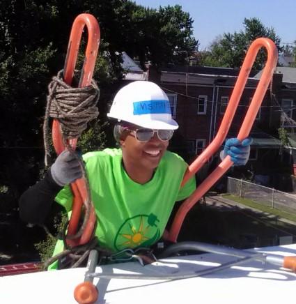 Homeowner Pamela peaks over the top of a ladder