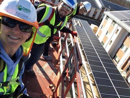 Kaly takes a selfie with volunteers with a solar carport in the background