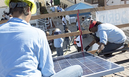 Two individuals work together on a solar panel