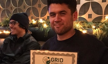 Peter Barragan smiles and holds a certificate for effort