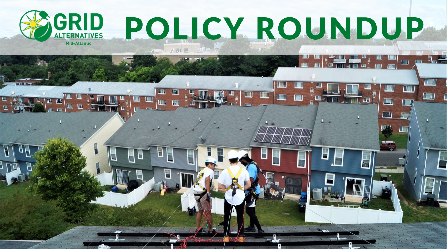 GRID Mid-Atlantic staff member Roy guides two volunteers on the roof during an install with the many homes of Lincoln Heights in the background.