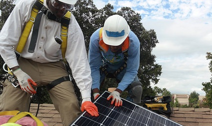 Construction workers with their legs spread apart on a roof hunch over a solar panel