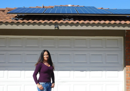 GRID client Priscilla Morrow-Moreno stands in front of her home with rooftop solar panels.
