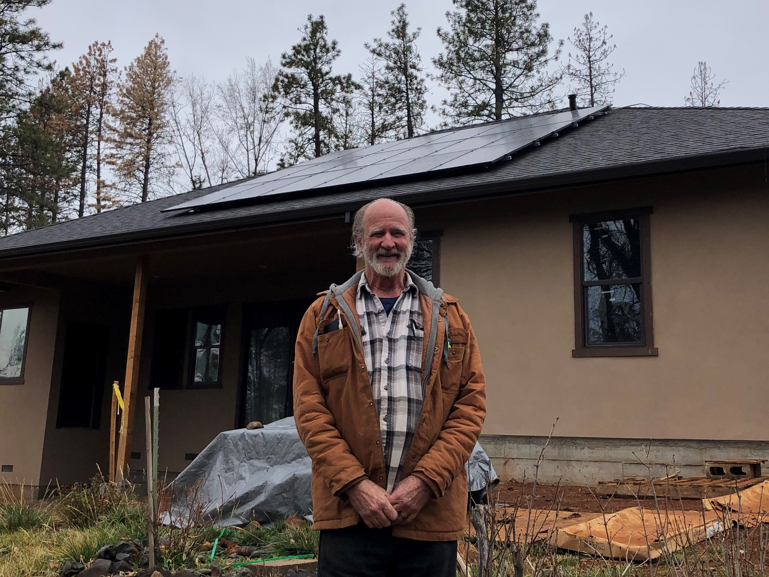Richard Stone standing in front of his new home in Paradise, CA with newly installed solar panels visible on the roof, tall trees in the background.