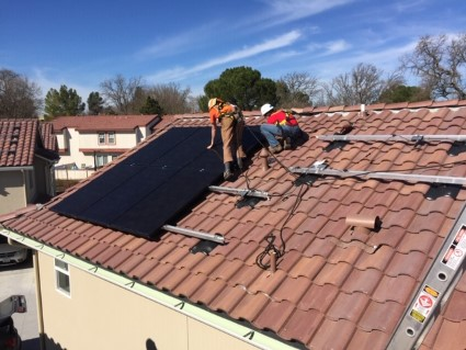 Community members install rooftop solar on the Rolling Hills apartment complex.