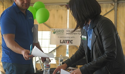 At a table in a tent, a person in a blue shirt hands over paperwork to another person with long hair, a GRID Alternatives top, and a black jacket