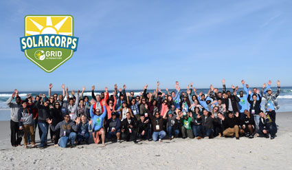 Large group of SolarCorps Fellows posing for a photo on the beach.