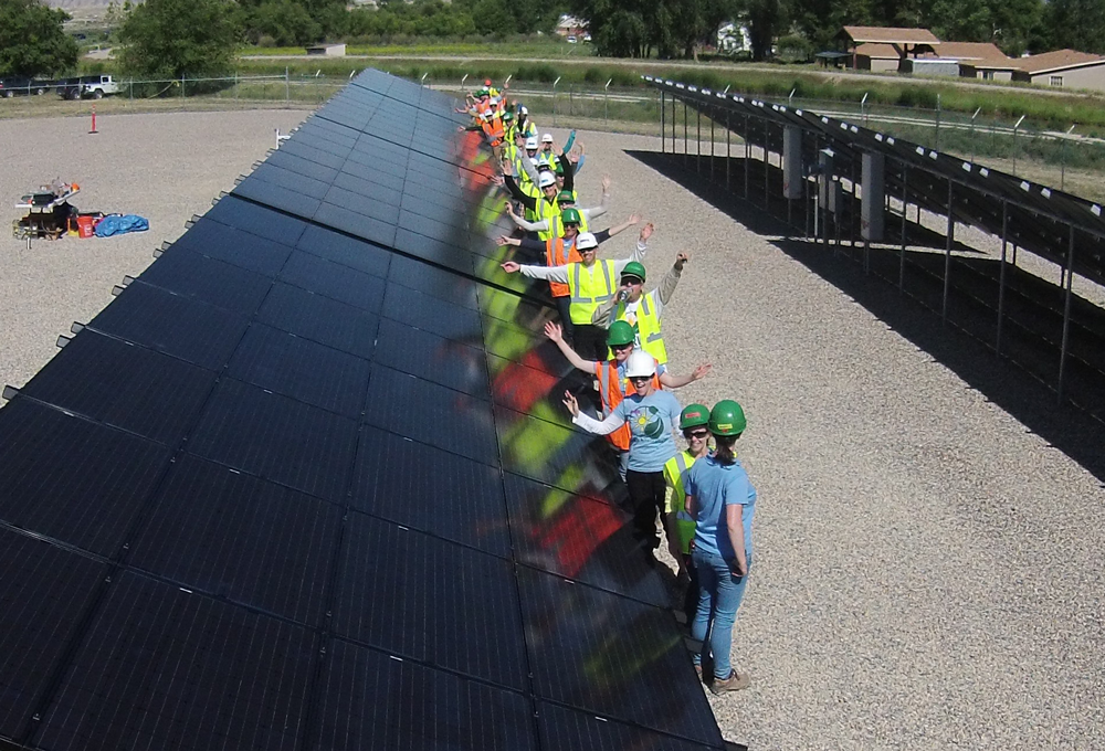 GRID volunteers next to solar panels.