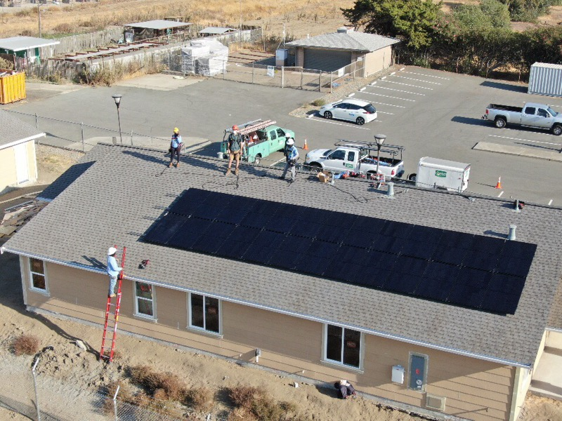 An aerial view of GRID Alternatives staff and the 26 solar panels installed at Rio Vista.
