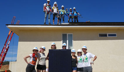Students from the University of Michigan pose with the final solar panel they installed on a home for a tribal family in San Diego.