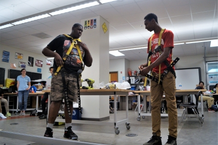 Two high school students demonstrate how to correctly wear a safety harness during a class presentation.