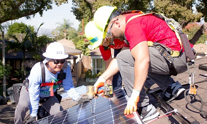"A Solar Installation Supervisor whose hat says ""Lee"" shows two people with red shirts on how to work with a drill on a roof"