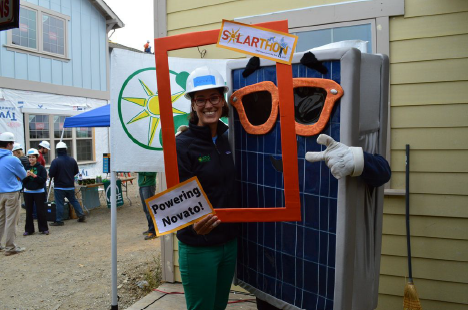 GRID Bay Area Regional Director Renee Sharp holds up an orange photo prop as she poses with Sunny the Solar Panel at the 2016 Solarthon installation site in Novato.
