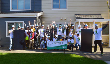 A group of SunPower employee volunteers pose with a banner in front of the Marcus Garvey apartment complex.