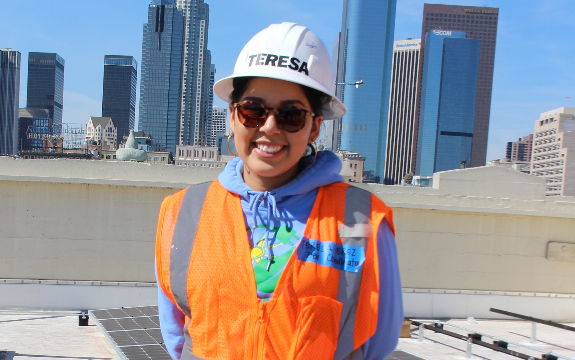 Teresa, identified by hard hat name, stands on a flat roof in front of skyline buildings