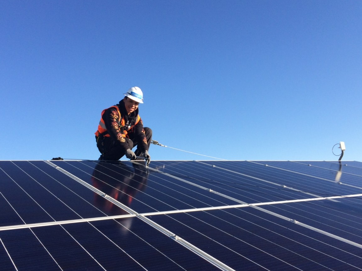 A trainee wearing an orange vest smiles while securing a solar panel on top of a roof. The sky is blue behind him.