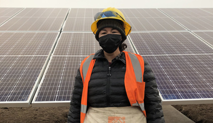 Tessa is wearing a yellow hard hat and orange safety vest. She's posing in front of a ground-mount solar array on a cloudy day.