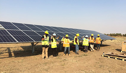 Solar trainees wearing safety vest and hard hats pose in front of a ground mount solar array