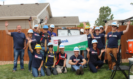 Group of 12 volunteers in dark blue shirts hold up U.S. Bank banner