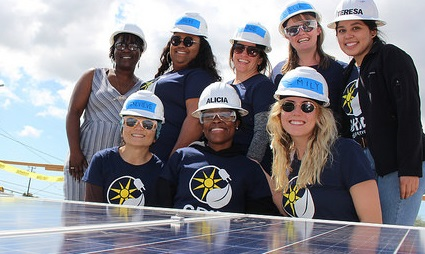 Women lined up in two rows behind an array of solar panels smile towards the camera with a blue sky in the background