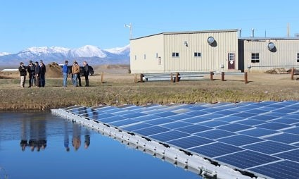 A floating solar system is in the foreground, with mountains in the background