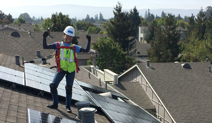 A young women (Winnie) stands on a rooftop next to solar panels with her arms outstretched.