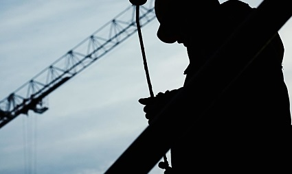 The silhouetted figure of a construction worker holds some wiring in hand