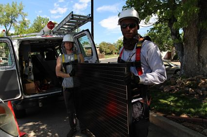 Two trainees carrying a solar module