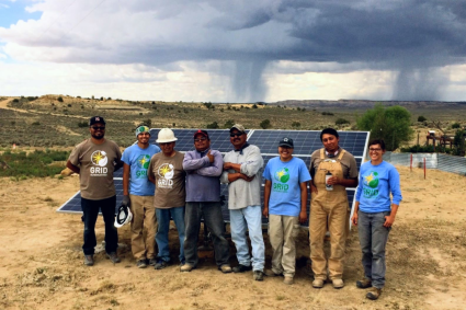 GRID staff and native veterans smile in front of a finished array with monsoon rain far off in the background.