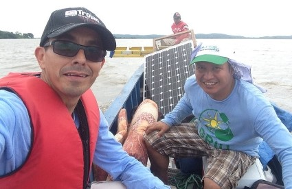 GRID staff in a boat with a solar panel and other equipment