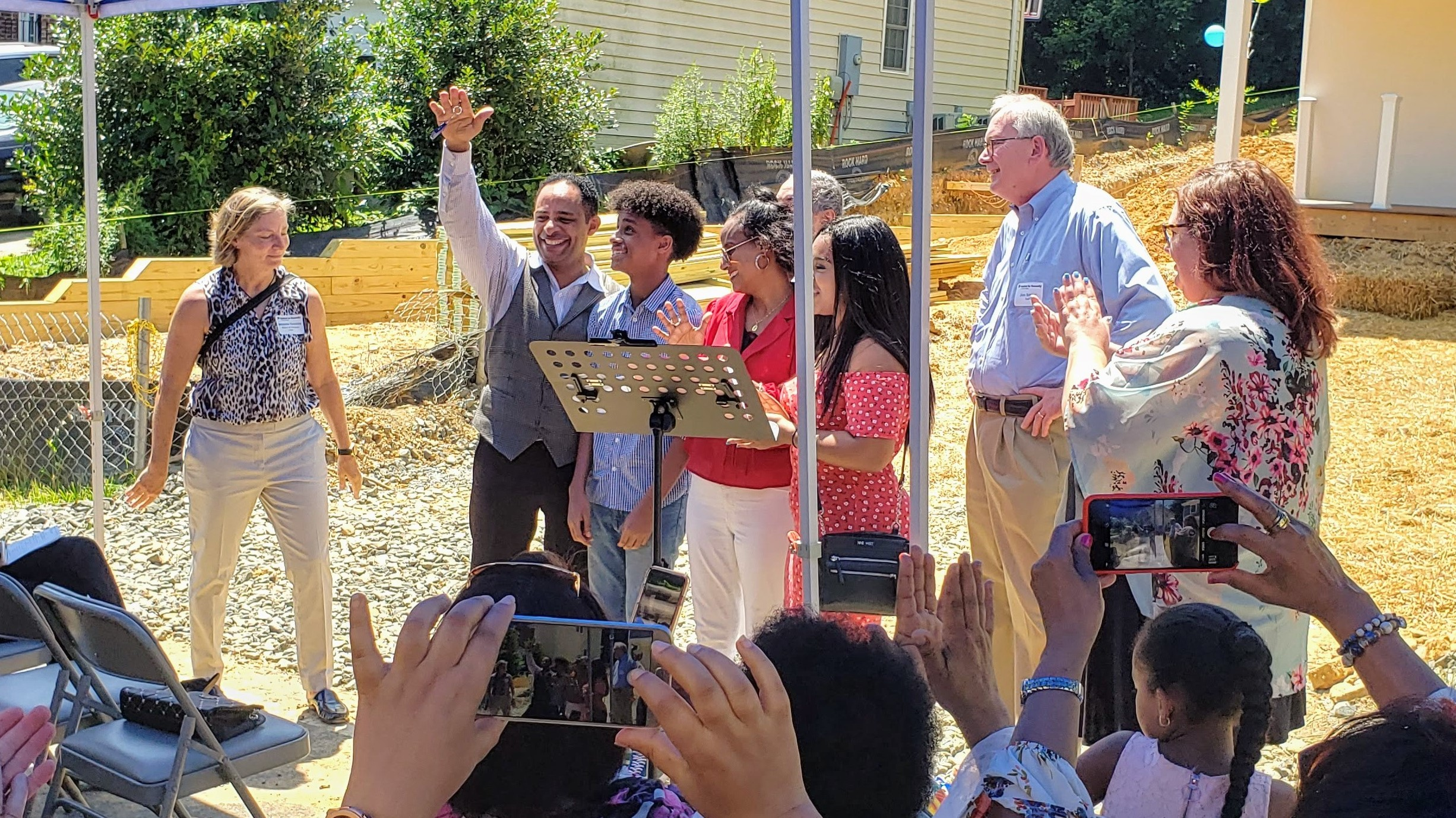 Tesfaye joyfully raises the keys to his new Habitat for Humanity home as a crowd applauds during a dedication ceremony in June.