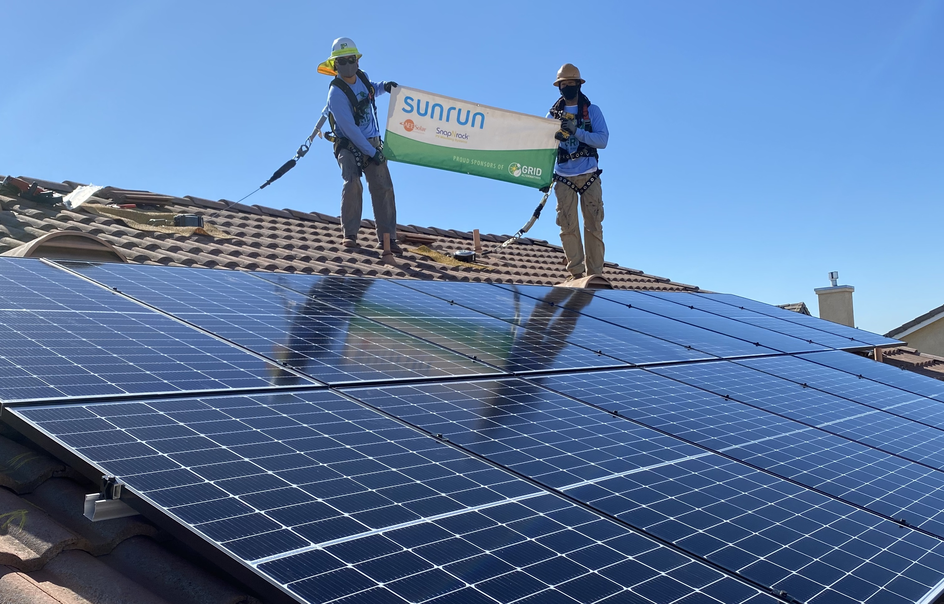 solar installers stand on roof with banner