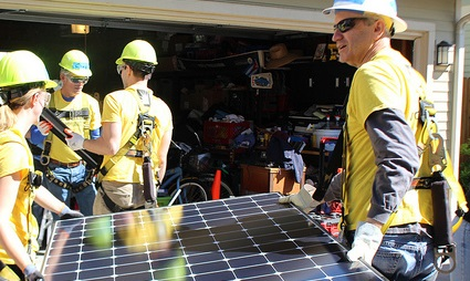 Two people in yellow shirts carry a solar panel