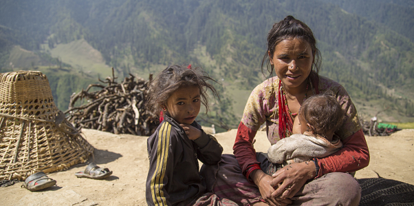 A mother breastfeeds her child in front of a mountainous landscape.