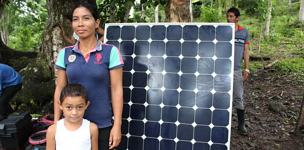 A San Jose family stands in front of their solar panel