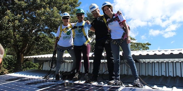 GRID participants installing solar on the roof of the coffee cooperative building