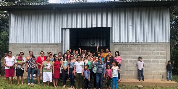 Members of the coffee cooperative standing in front of the new building constructed for the coffee roaster.