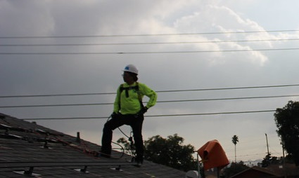A person stands in front of cloudy skies on a composite shingle roof