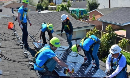 On a roof, a person doing construction in a black sweater gives instructions to various other people doing construction in blue team shirts