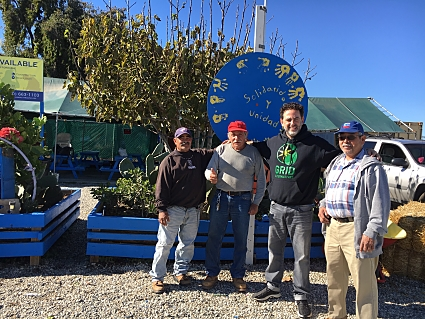A GRID Alternatives employee in a sweatshirt stands with three workers at an outdoor site