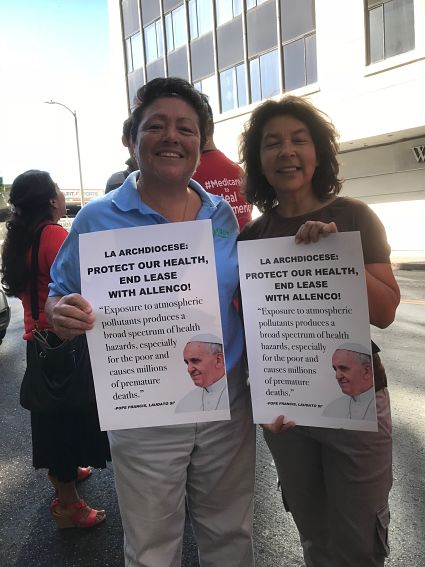 """Two individuals supporting action by the Archdiocese hold up signs that say, """"LA Archdiocese: Protect our health, end the lease with AllenCo"""""""
