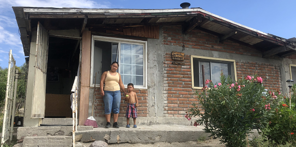 A mother and son stand in front of their house in Santa Catarina.
