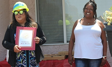 Smiling, a white-shirted homeowner accepts a certificate from another person wearing a safety helmet and dress