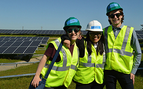 Three people in hard hats smile in front of field of solar panels
