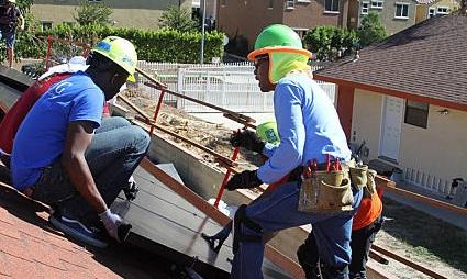 A Solar Installation Supervisor instructs a Solarthon volunteer