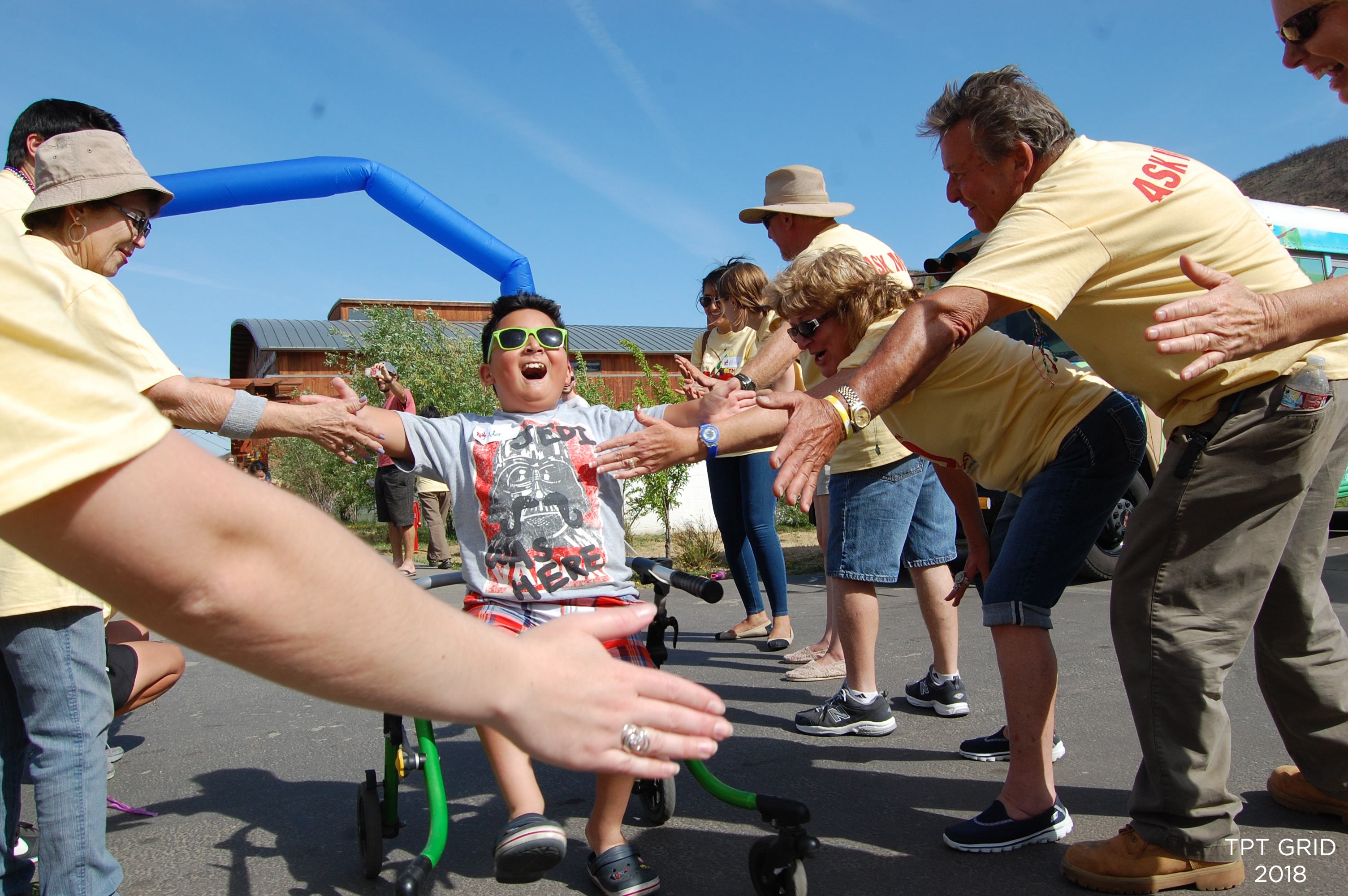 A child in a wheelchair looking happy rolls down a row of cheering camp adults