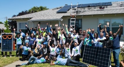 A Group of people pose in front of a single family home with solar energy on the roof.